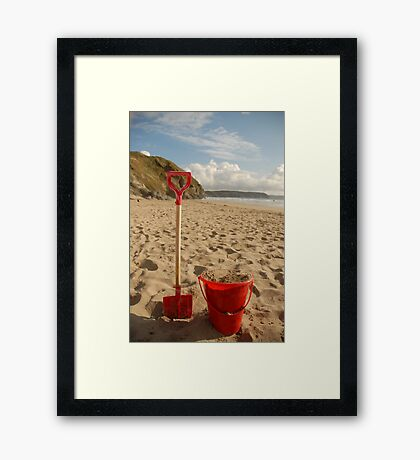 Red bucket and spade in the sand on the beach Framed Print