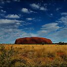 Ayers Rock under a cloudy blue sky - not common by mashdown