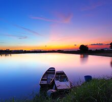 Sunset along the pond with two boats and two magical color on sky by kawing921