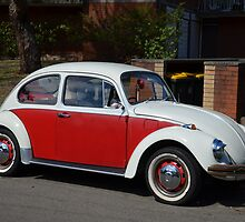 Old red and white Volkswagen Beetle car by Paul Watson