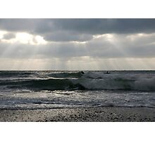 Surfers in winter with rays of sunlight, Wembury, near Plymouth, Devon, UK Photographic Print