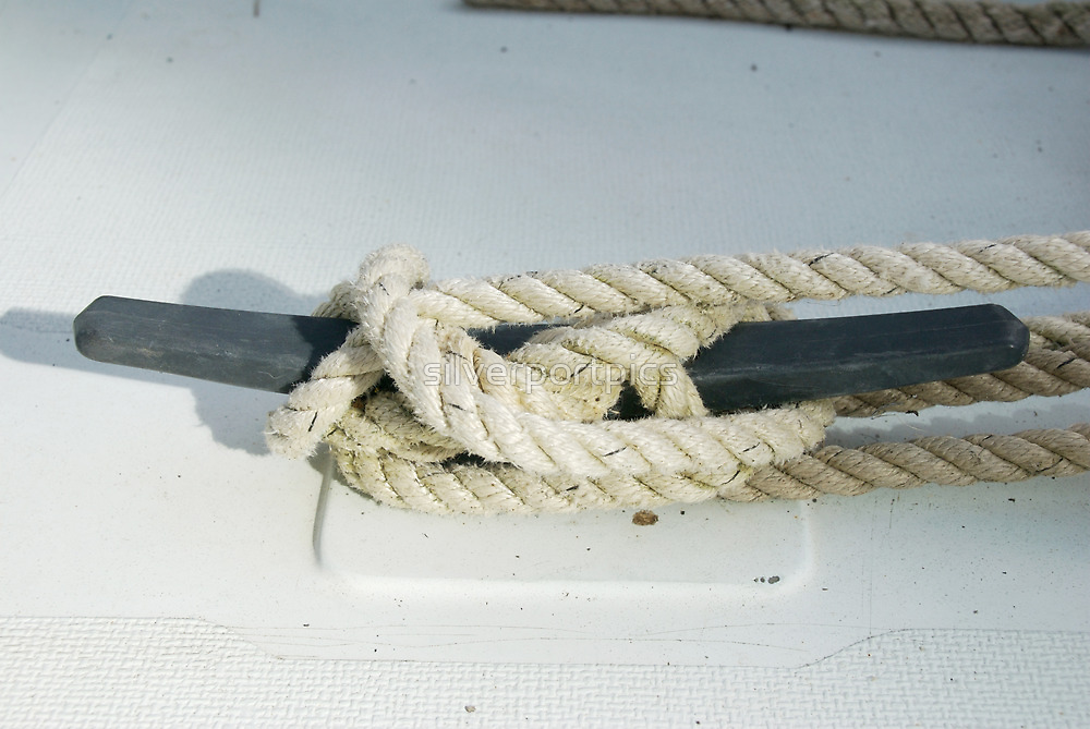 Rope tied fast around boat cleat by silverportpics