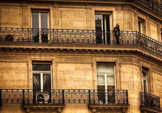 A woman texting on her balcony in Paris, France by Elana Bailey