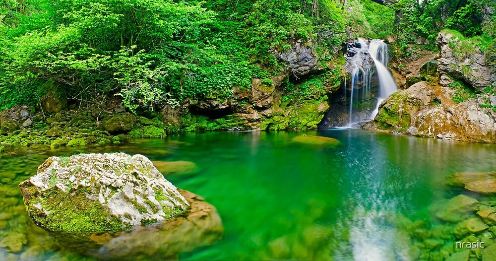 Beatiful waterfall falling into peaceful river by nrasic