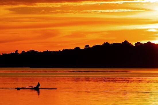 Man rowing and training at sunset by nrasic
