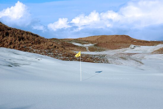 snowfall covered links golf course with yellow flag by morrbyte