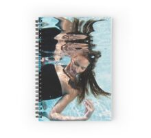 A young woman in evening dress floats underwater  Spiral Notebook