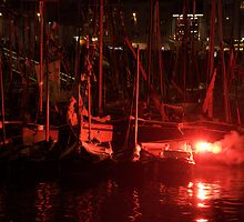 Red flare in front of boat masts in harbour, Brest 2008 Maritime Festival, France by silverportpics