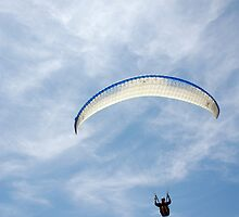 Parascender in mid flight with blue and white canopy in sunshine by silverportpics