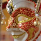Red and gold Venetian mask in a novelty shop. by Debu55y