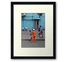 woman sweeps, man minds his bike.  Framed Print