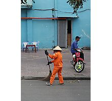 woman sweeps, man minds his bike.  Photographic Print