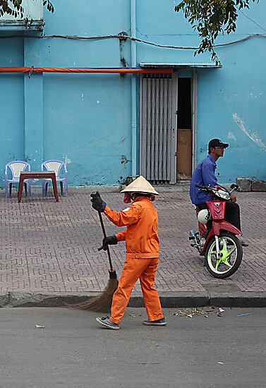 woman sweeps, man minds his bike.  by geof