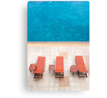 poolside deckchairs alongside blue swimming pool from top view Canvas Print
