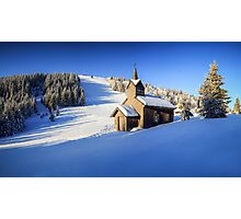 Winter chapel on the hill in the Alps Photographic Print