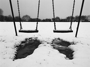 Swings in thawing snow by Andy Stafford