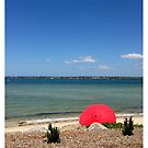 red umbrella on beach by kathybellingham