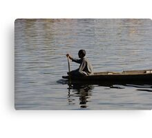 Splashing in the water caused due to Kashmiri man rowing a small wooden boat Canvas Print