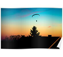 Paraglider flying over the rooftops at sunset Poster
