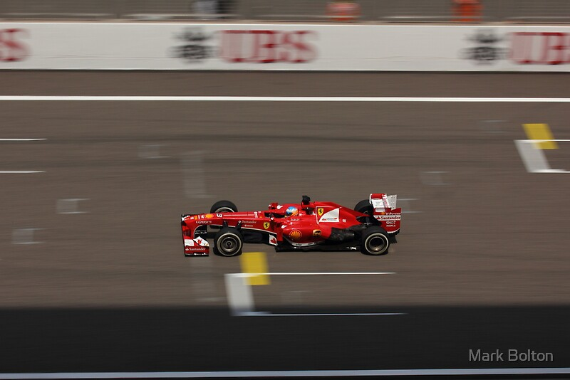 Fernando Alonso's Scuderia Ferrari passes the Pit Wall
