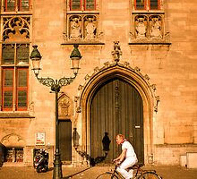 A local rides his bike in the square in Bruges by Elana Bailey