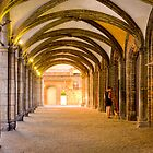 A woman with her dog in the archways of Bruges by Elana Bailey