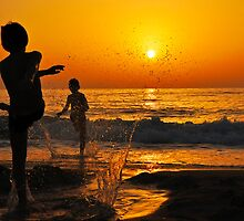 children playing on the Beach at sunset by PhotoStock-Isra