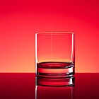 Glass tumbler on red by Bob Noble