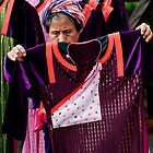 Thai Akha Woman Picking Out Fabric by Duane Bigsby