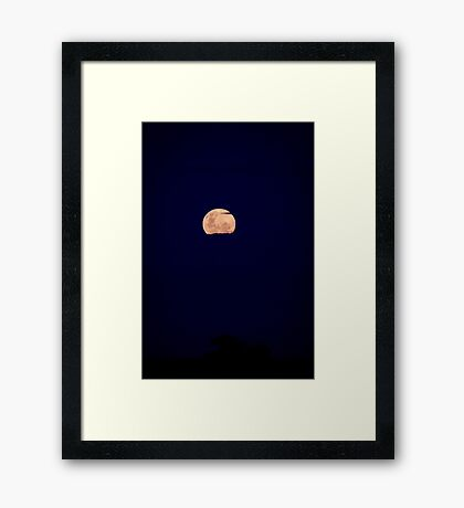 Supermoon above the land peaking out from the clouds Framed Print