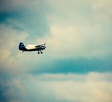 Propeller Biplane In Blue Sky Over Clouds by GrishkaBruev