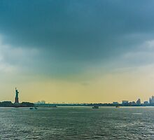 New York, the statue of liberty and Manhattan at sunset. by Giuseppe Milo