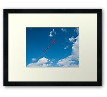 Flying red heart - shaped kyte on a clear blue sky Framed Print