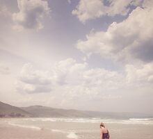 Girl Walking Along a Beach by jamjarphotos