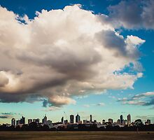 Enormous clouds dwarf a city skyline by jamjarphotos
