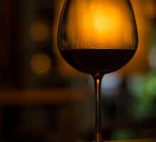 red wine glass in cozy dark bar by jackmalipan