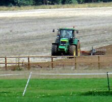 the tractors ploughing the fields ready for the next crop by margaret hanks