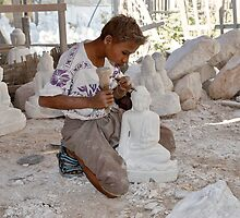 a boy chisels in workshop of Buddha Statues by travel4pictures