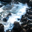 A wave breaks onto the rocks by Richard Flint