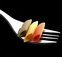 italian penne pasta on a fork on black background by keko64