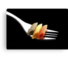 italian penne pasta on a fork on black background Canvas Print