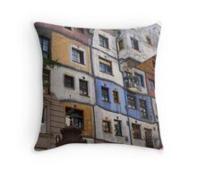 Front of a colourful building by Hundertwasser with a sign, Vienna Throw Pillow