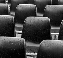 Plastic black chairs under rain by Daniele Zighetti