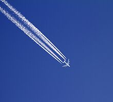 Airplane with condensation trails on blue sky. by cloud7