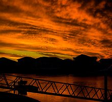 Red sunset with storm clouds over canals in Queensland. by twoorthreeor