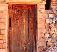 Old wooden door and stone house by Roupen  Baker