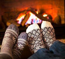 Feet warming by fireplace by Elena Elisseeva