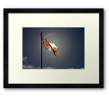Sun shining through a flying flag Framed Print