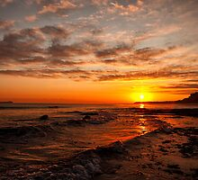 Sunrise across the waves to Bamburgh Castle, Northumberland, UK by Mark Kenwood