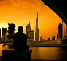Man watching sunset behind the world's tallest tower Burj Khalifa in Dubai by naufalmq